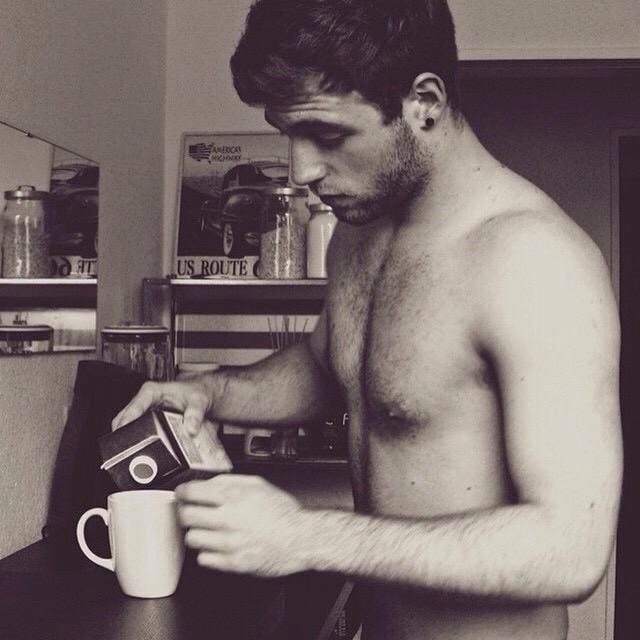Naked handsome guy drink